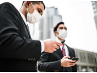 Japanese businessmen wearing masks to avoid getting the flu in the city. Source: iStock by Getty Images; Copyright: franckreporter; URL: https://www.istockphoto.com/jp/en/photo/japanese-business-man-on-the-phone-on-the-city-gm469631656-62474182; License: Licensed by the authors.