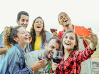 A group of people laughing, drinking, and posting photos (ie, alcohol posts) on social media. Source: Shutterstock; Copyright: Alessandro Biascioli; URL: https://www.shutterstock.com/nl/image-photo/group-happy-friends-taking-selfie-using-1050749291; License: Licensed by the authors.