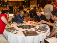 Adults playing tabletop board game at gaming convention. Source: Flickr; Copyright: dooley; URL: https://www.flickr.com/photos/dooleynoted/21607509202; License: Creative Commons Attribution (CC-BY).