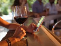 Source: Bigstock; Copyright: Wavebreak Media Ltd; URL: https://www.bigstockphoto.com/image-198974353/stock-photo-hand-of-woman-using-mobile-phone-while-having-a-glass-of-wine-in-restaurant; License: Licensed by the authors.